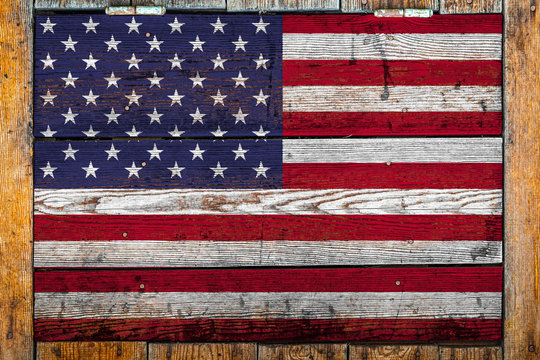 National flag of USA on a wooden wall background.The concept of national pride and symbol of the country.Flag painted on a wooden fence with metal nails.