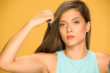 Young beautiful woman combing her hair on yellow background