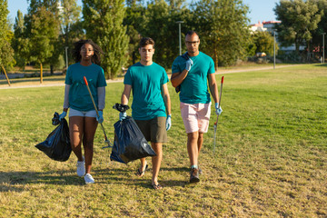 Serious volunteers carrying garbage from city park. Young woman and men walking through city lawn,...
