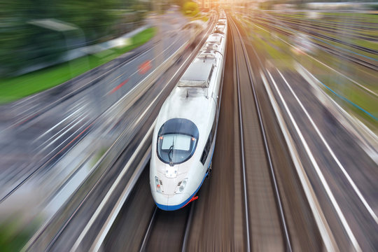 Railroad travel high speed fast train passenger locomotive motion blur effect in the city, top aerial view from above.