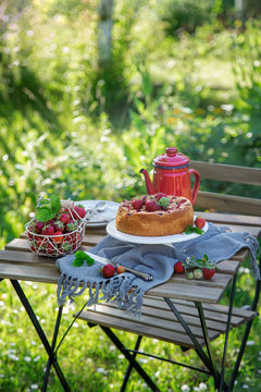 Table setting with summer strawberry cake in a garden
