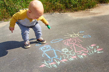 Little boy drawing with chalk on the asphalt, happy family: dad, mom and baby outdoors