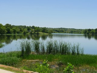 Wide view of Veteran Lake in Sulphur, Oklahoma with green grasses from the road