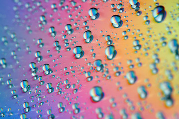 Water drops with reflection of the rainbow. Colorful abstract background. Blue, green, red and yellow abstract rainbow background. Closeup, selective focus
