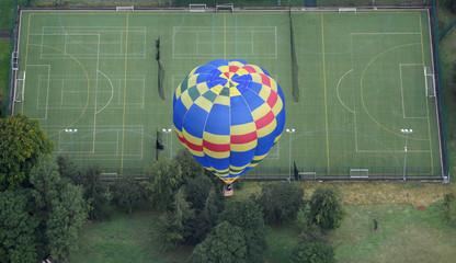 A balloon flies above a sports ground at the annual Bristol hot air balloon festival in Bristol, Britain