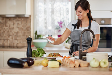 Cute Caucasian brunette in apron standing in kitchen and adding salt in fresh delicious pasta. Preparation of italian food concept.