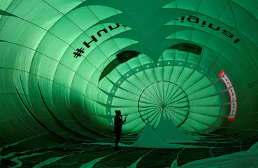 A man films inside a partially inflated balloon during a mass take off at the annual Bristol hot air balloon festival in Bristol