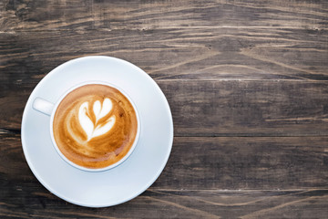 Fotobehang - Fresh cappuchino or flat white coffee in a white cup with latte art on it,