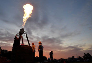 A crew tests a burner as balloons launch during a mass take off at the annual Bristol hot air balloon festival in Bristol