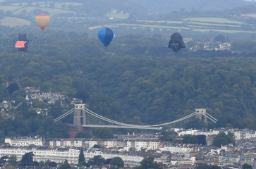 Balloons, including one shaped as the head of fictional Star Wars film character Darth Vader, fly near the Clifton Suspension Bridge during a mass take off at the annual Bristol hot air balloon festival in Bristol