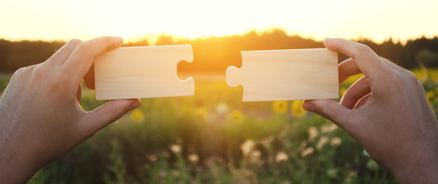 A man collects collects wooden puzzles at sunset. Concept of success, business solutions. Strategy and goal achievement. Making the right decision. Connection and partnership. Selective focus