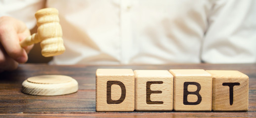 Wooden blocks with the word Debt and judge with a gavel. The concept of judicial punishment for...