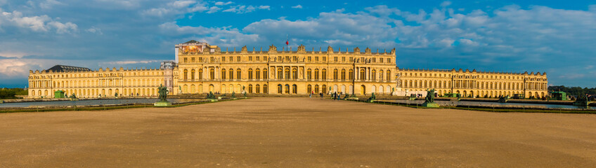 Great sunset panorama picture of the west facade of the famous Palace of Versailles from the Water Parterre with the two large rectangular pools and the gravel path in the middle.