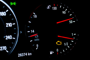 Selective focus of malfunction check engine warning light on car dashboard. Side view of modern car instrument panel with odometer, car water temperature, car voltmeter and fuel gauge.