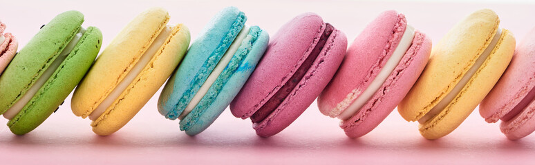 row of delicious French macaroons of different flavors on pink background, panoramic shot Wall mural