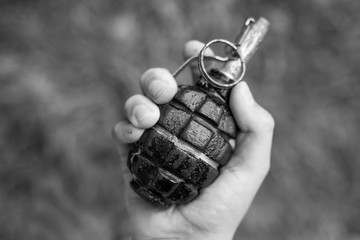Closeup top view of white kid hand holding real old grenade. Horizontal black and white photography.
