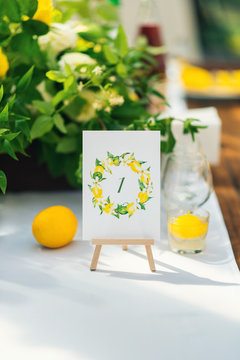 Elegant wedding table arrangement, floral decoration, restaurant. Wedding table setup. Wedding in the forest. Seat numbers. Lemon theme