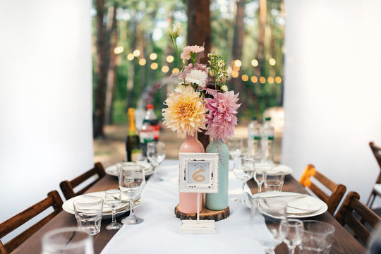 Elegant wedding table arrangement, floral decoration with peony, restaurant. Wedding table setup. Wedding in the forest. Seat numbers.