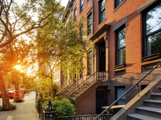 Old brownstone buildings along a quiet neighborhood street in Greenwich Village, New York City NYC