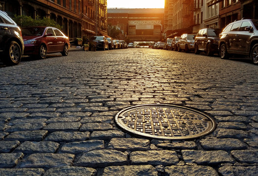 Sunlight shining on a cobblestone street and manhole cover in New York City
