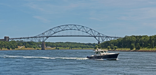 A pleasure craft passes through the Cape Cod Canal in Massachusetts with the Sagamore Bridge in the background.