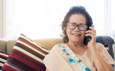 Old woman is happy for using mobile phone at home