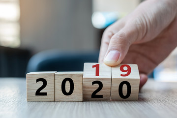 Business man hand holding wooden cube with flip over block 2019 to 2020 word on table background....