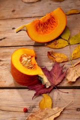 fresh pumpkin and leaves on the wooden background