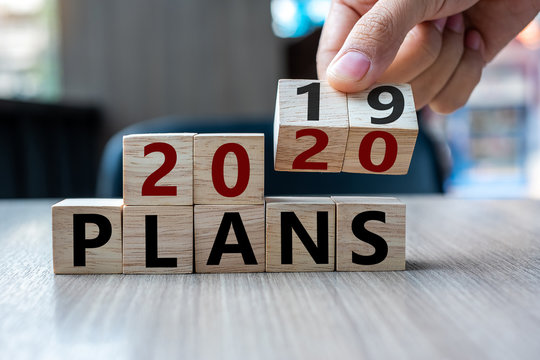 Business man hand holding wooden cube with flip over block 2019 to 2020 Plans word on table background. Resolution, strategy, solution, goal, business and New Year holiday concepts