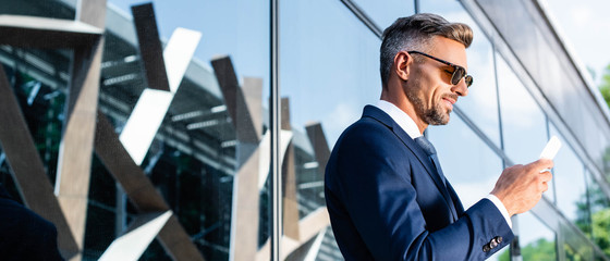 panoramic shot of handsome man in suit and glasses using smartphone