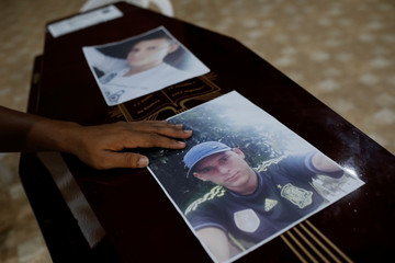 Pictures of Efraim Mota are seen on his coffin during a wake in Altamira