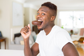 African american man eating  and enjoying a sweet chocolate donut