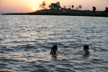 Girls swim during sunset at Lake Habbaniyah