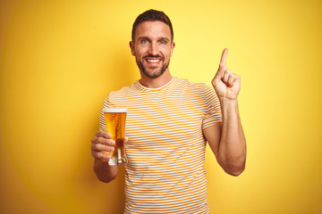 Young handsome man drinking a pint glass of beer over isolated yellow background very happy pointing with hand and finger to the side