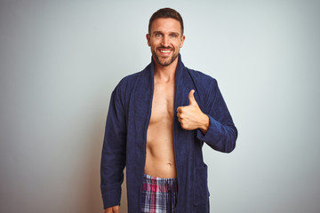 Sexy shirtless man wearing comfortable pajamas and robe over isolated background doing happy thumbs...