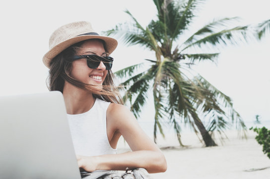 Young woman in a hat working with laptop computer on tropical island beach under palm trees Freelance  concept