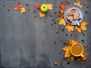 Wall Mural - Seasonal autumn background. Frame of colorful maple leaves and a cup of hot drink, coffee, latte or cappuccino, nutmeg, cake, apple and cinnamon over grey.