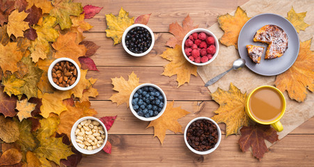 Wall Mural - Seasonal autumn background. Frame of maple leaves and a cake and berries over wooden background.