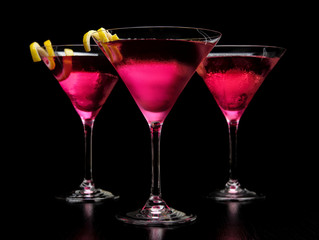 Closeup three cosmopolitan cocktails on black board