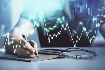 Multi exposure of woman's hands making notes with forex graph hologram. Concept of technical analysis.