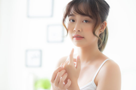 Beautiful asian woman applying cream and treatment for skin care touch on hand, asia girl with lotion spa and moisturizing for health and wellness body part, lifestyle and beauty cosmetic concept.