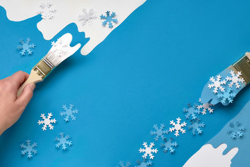 Background in blue and white with brushes loaded with paper snowflakes, copy-space