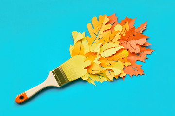 Top view of brush loaded with Autumn leaves on blue paper background