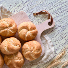 Crusty round bread rolls, known as Kaiser or Vienna rolls on linen towel