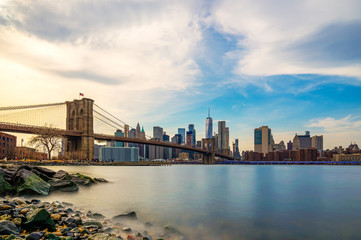 Fototapete - Beautiful sence of Brooklyn bridge and lower manhattan of New York city in dusk evening. Downtown of lower Manhattan of New York city and Smooth Hudson river with sunset light.