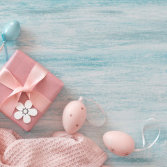 Wrapped gift box, decorative flowers and Easter eggs. Easter flat lay in pastel colors with copy-space.