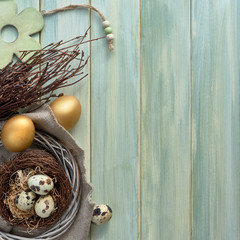 Easter flat lay on light green wooden planks with quail eggs in the nest and two golden eggs, text space