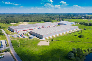 Aerial view of goods warehouse. Logistics center in industrial city zone from drone view. Background texture concept. Wall mural
