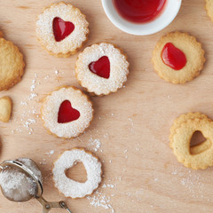 Top view of traditional Linzer cookies filled with strawberry jam on wooden board with heart-shaped openings