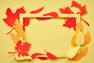 Flat lay on yellow paper, paper frame with red and orange Autumn leaves